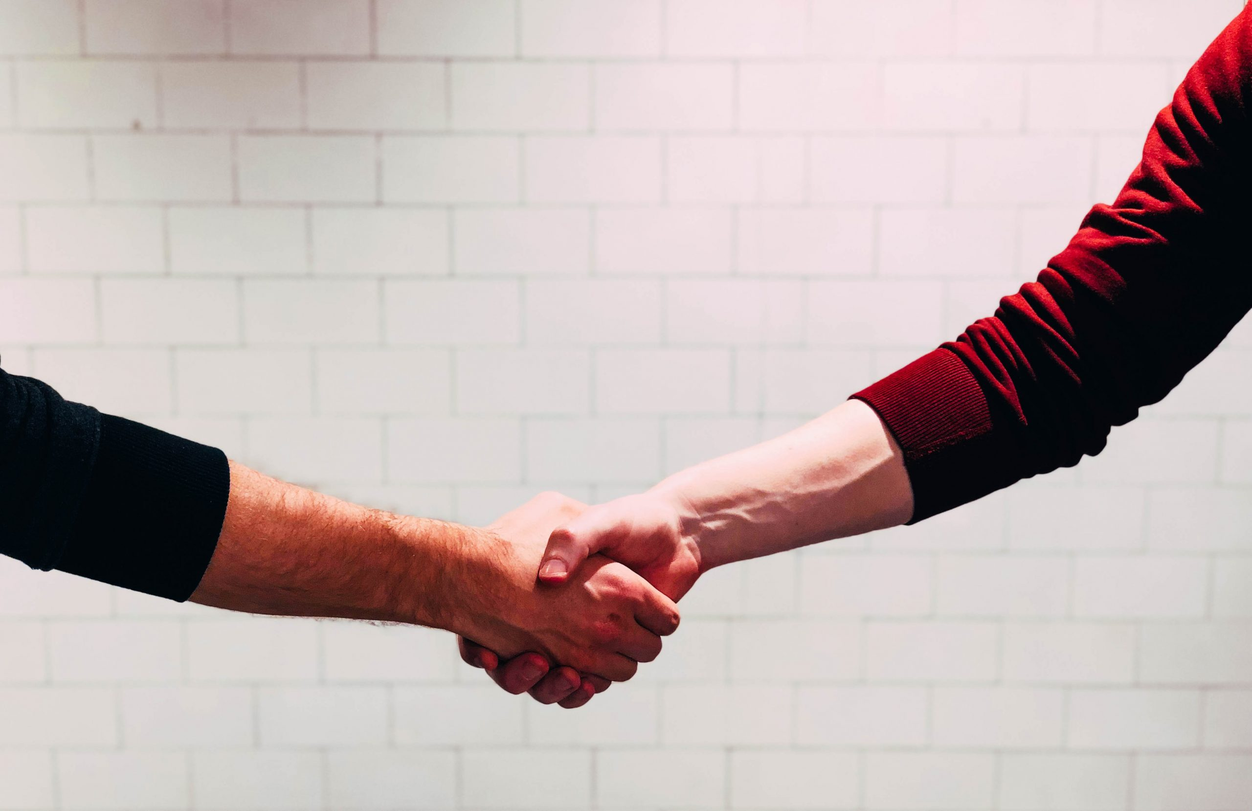 Two people shaking hands in front of a white wall.