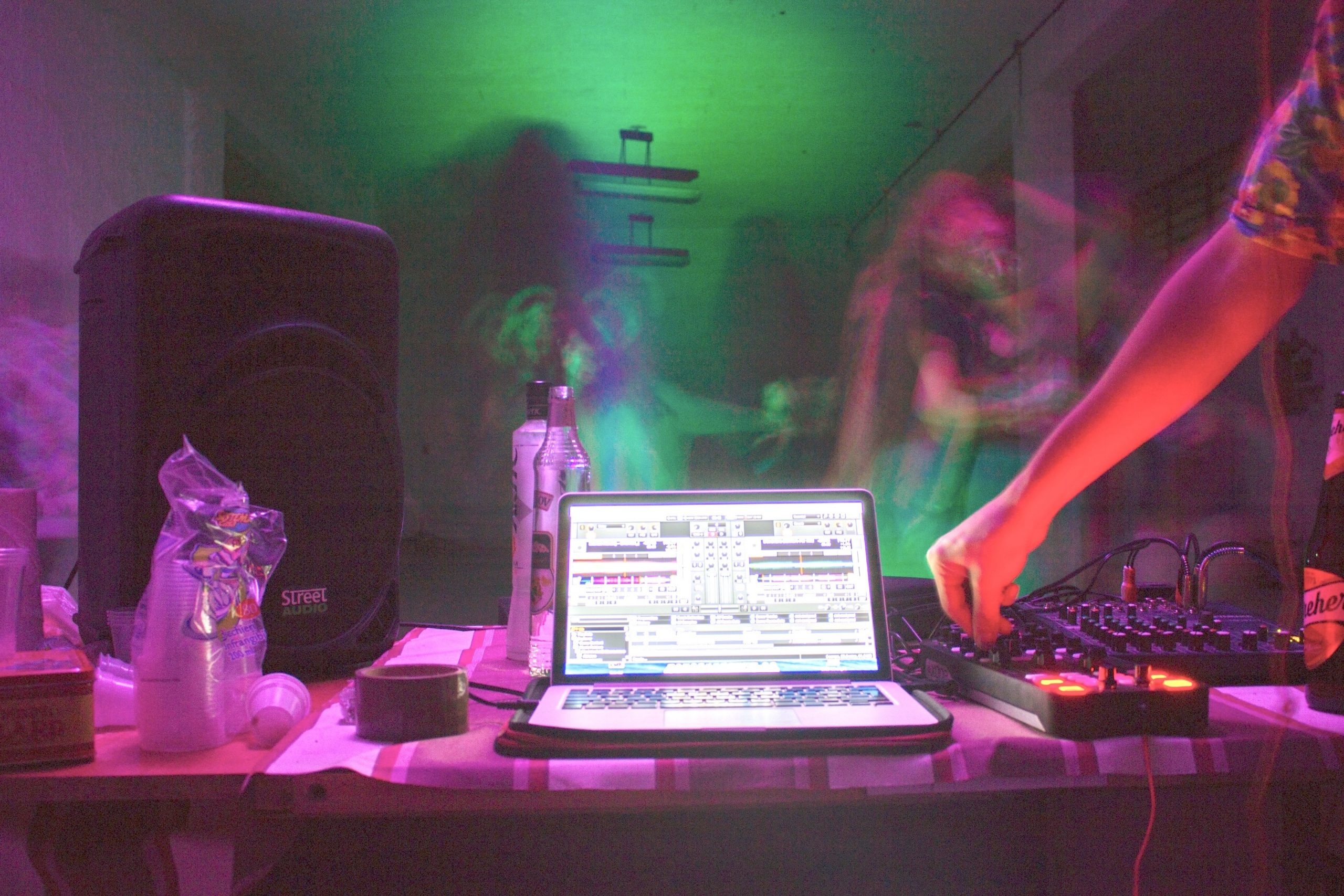 Photo of man DJing on his laptop at home.