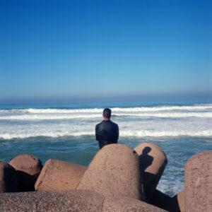 A man sits near the ocean. Casablanca, Morocco