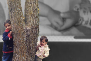 Picture of Khadija and Fatima with a tree in front of a picture of them holding hands.