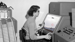 Vintage photo of a woman at a computer with an image of a UFO collaged onto her screen.