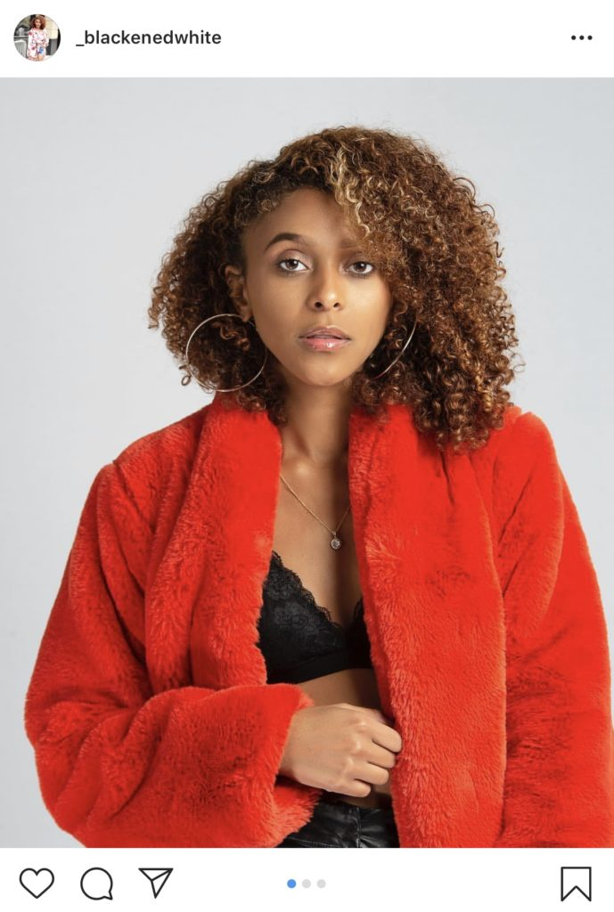 A woman in a red jacket with gold hoop earrings.